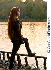 Beautiful-haired woman looking at the lake