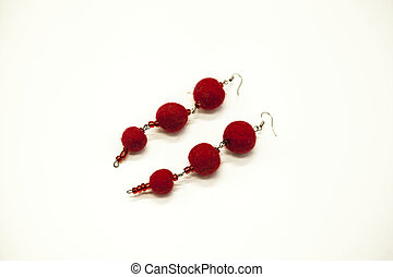 Beautiful hand-made earrings felted wool sheep red shades on a white background, close-up.