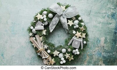 Beautiful, handmade Christmas wreath made with wooden decorations, balls, stars and bow. Placed on stone background. Top view, flat lay.