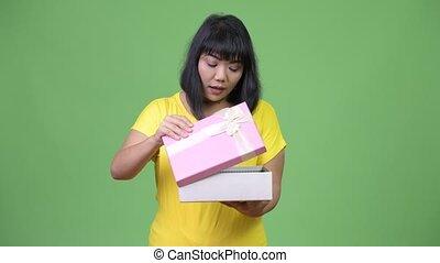 Beautiful happy Asian woman opening gift box