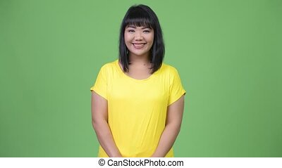 Beautiful happy Asian woman smiling against green background