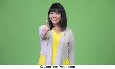 Beautiful happy Asian woman smiling while giving thumbs up