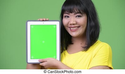 Beautiful happy Asian woman smiling while showing digital tablet