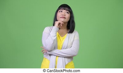 Beautiful happy Asian woman smiling while thinking
