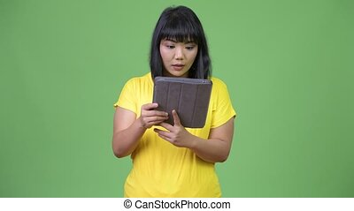 Beautiful happy Asian woman using digital tablet and looking surprised