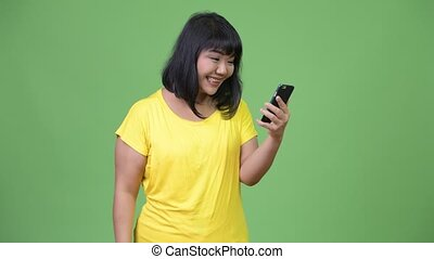 Beautiful happy Asian woman using phone and getting good...