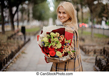 Beautiful happy blonde woman in plaid coat holding a bright bouquet of flowers walking on alley