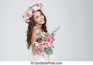 Beautiful happy bride in rose wreath holding bouquet of ...
