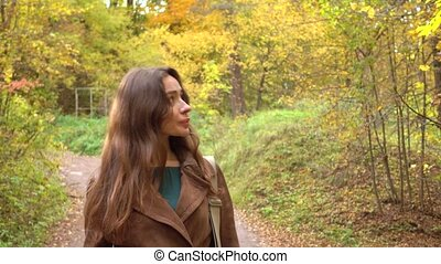Beautiful happy brunette girl walking through autumn woods....