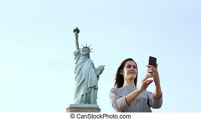 Beautiful happy Caucasian tourist woman takes a selfie photo with smartphone at Statue of Liberty in New York City.