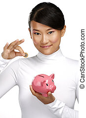 Beautiful happy chinese girl showing a piggybank