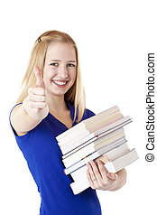 Beautiful, happy female student with books shows thumb up