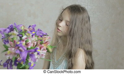 Beautiful happy girl enjoys bouquet flowers of irises and...