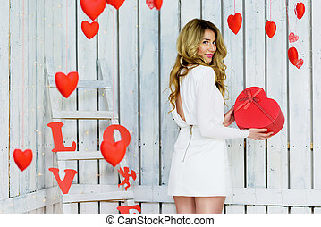 Beautiful Happy girl holding a heart giftbox