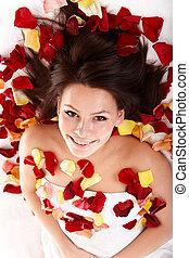 Beautiful happy girl in rose petal. Spa .