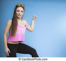 Beautiful happy girl in summer clothes pointing with finger