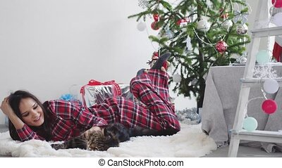 Beautiful happy girl lying beside Christmas fir-tree on a rug in pajamas playing with Maine Coon cat. slow motion. 3840x2160