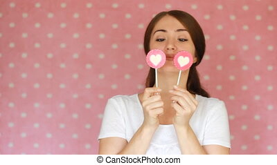 Beautiful happy girl smiling, winks and looking at the camera. A young woman is holding a candy in the shape of a heart. The concept of love, good mood, coquetry flirt, flirting.