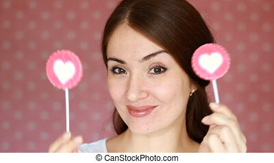 Beautiful happy girl smiling, winks and looking at the camera. A young woman is holding a candy in the shape of a heart. The concept of love, good mood, coquetry flirt, flirting