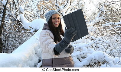 Beautiful happy girl talking on Skype on the tablet. Snow...