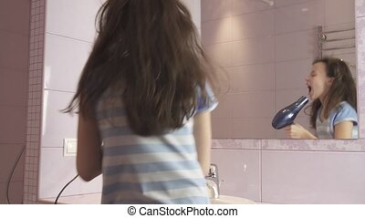 Beautiful happy girl teenager dries hair with hair dryer and sings and dances in front of a mirror in the bathroom stock footage video