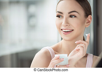 Beautiful happy girl using cosmetics for skin