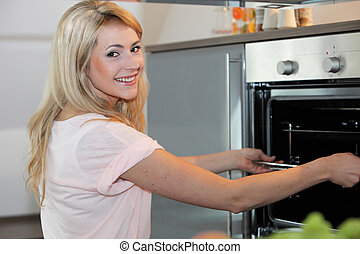 Beautiful happy housewife cooking a meal