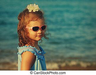 Beautiful happy kid girl in glasses looking on sea background. Vintage portrait