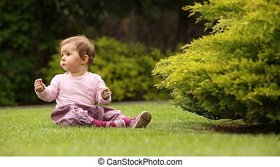 Beautiful happy little baby girl sitting on a green meadow...