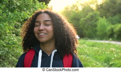 Beautiful happy mixed race African American girl teenager female young woman hiking with red backpack in the countryside at sunset or sunrise