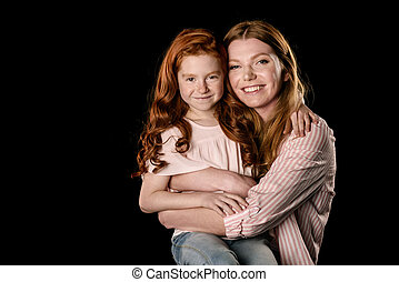 c17d9632d4 Beautiful happy mother and daughter hugging and smiling at camera isolated  on black