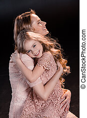 Beautiful happy mother and daughter hugging on black