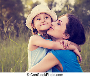Beautiful happy mother hugging and kissing her grimacing fun daughter on summer bright background. Closeup toned portrait