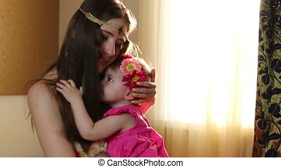 Beautiful happy mother hugging baby girl with love. Mom plays with her daughter in the nursery near the window