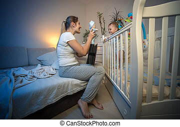 Beautiful happy mother playing with her baby boy in crib at night