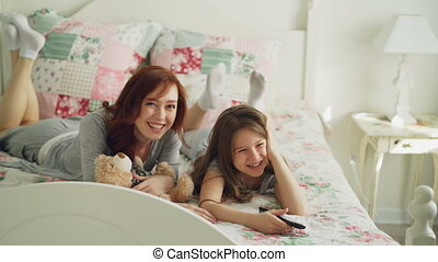 Beautiful happy mother with little daughter watching cartoon movie on TV and laughing while lying on bed at home in the morning in cozy bedroom