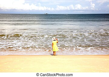 Beautiful happy multiracial Asian girl in vintage dresses standing on the beach.