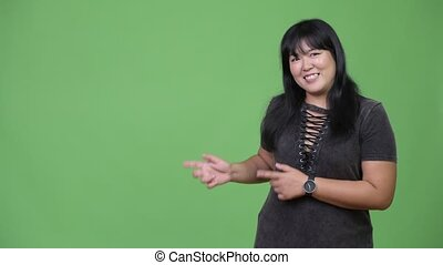Beautiful happy overweight Asian woman showing something -...