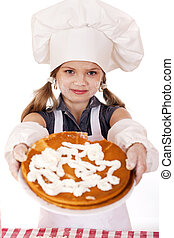 Beautiful happy seven year old girl in chef uniform with shortcakes and whipped cream