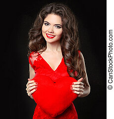 Beautiful happy smiling girl in red dress holding valentine's heart. Brunette with long curly hairstyle and red lips isolated on black background.