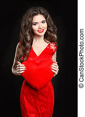 Beautiful happy smiling girl model with valentine heart in red dress