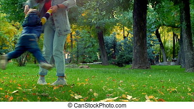 Beautiful Happy Smiling Stylish Joyful European Cute Mother in a Denim Suit and Long Curly Hair Walks Through the Autumn Park with a Beautiful Little Son of Two Years, Mom and Baby Dancing. Family Concept