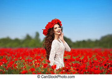 Beautiful happy smiling teen girl portrait with red flowers on head enjoying in poppies field nature background.