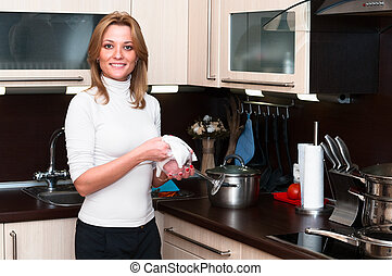 Beautiful happy smiling woman in kitchen interior. One...