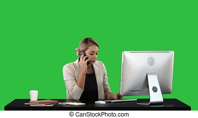Beautiful happy smiling young office woman working on computer at office desk Attractive cheerful model in formal wear using smartphone and computer, making call during workday on a Green Screen, Chroma Key.