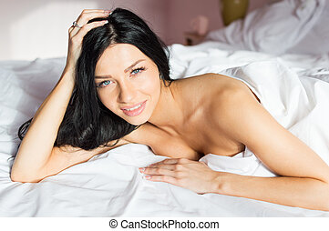 Beautiful happy smiling young woman in bed looking at camera