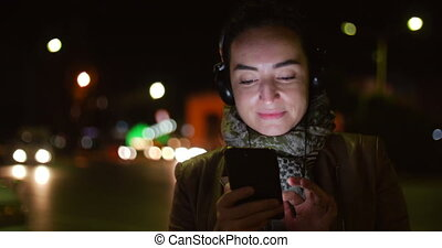 Beautiful Happy Stylish Young Pretty Girl in Jacket with White Headphones and Long Dark Hair Messaging on the Smart Phone and Listening to Music on the Background of the Night or Evening City