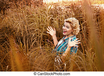beautiful happy surprised pinup girl standing alone at grass