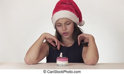 Beautiful happy teen girl in a Santa Claus hat dreams of a...