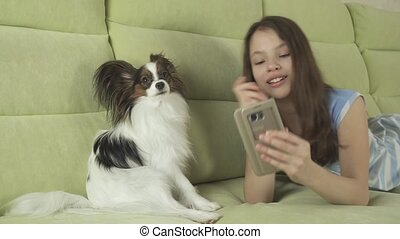 Beautiful happy teenage girl communicating in smartphone and with her dog stock footage video